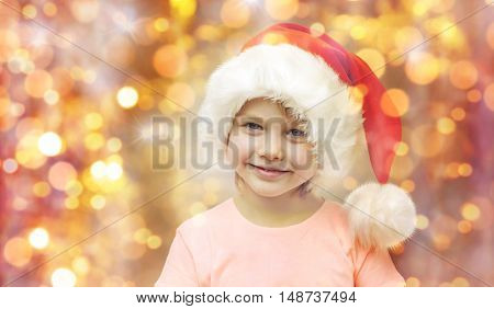 holidays, christmas, childhood and people concept - smiling little girl in santa hat sitting on couch over lights background
