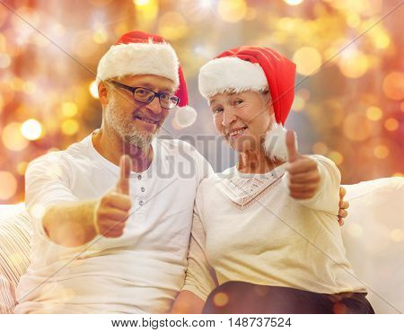 family, holidays, christmas, age and people concept - happy senior couple in santa helper hats sitting on sofa and showing thumbs up gesture over lights background