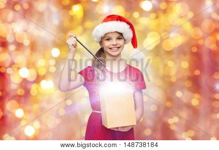 christmas, holidays and children concept - smiling girl in santa helper hat with gift box and magic wand over lights background