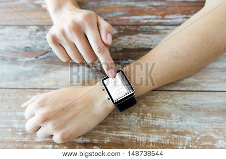 business, modern technology, programming and people concept - close up of female hands setting smart watch with coding on screen on wooden table