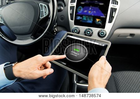 transport, business trip, modern technology and people concept - close up of male hands holding tablet pc computer with start engine button on screen in car