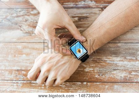 business, modern technology, media and people concept - close up of male hands setting smart watch with music player on screen on wooden table