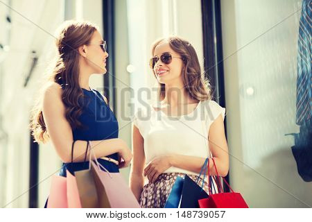 sale, consumerism and people concept - happy young women with shopping bags talking at to shop window in city
