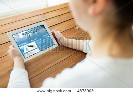 technology, people and mass media concept - close up of woman with world news web page on tablet pc computer screen on wooden table