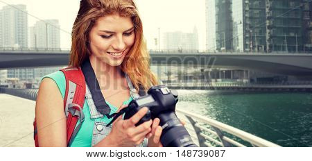 adventure, travel, tourism, hike and people concept - happy young woman with backpack and camera photographing over dubai city waterfront and bridge background