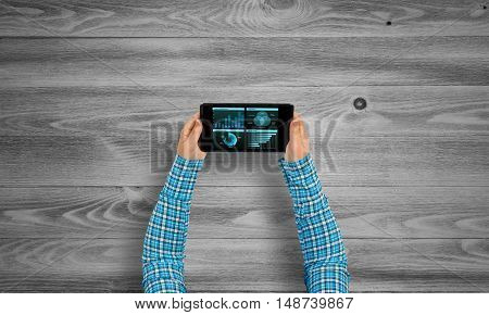 Top view of girl hands using tablet pc with diagrams and graphs on screen