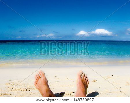 male feet at the sandy beach - legs of trousers
