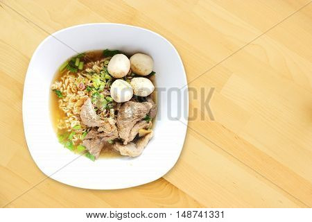 Top View Spicy Rich Flavour Noodle With Sliced Pork and Pork Balls Street Food Style On Wooden Background