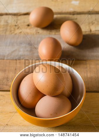 Chicken eggs in the bowl and on wooden table.
