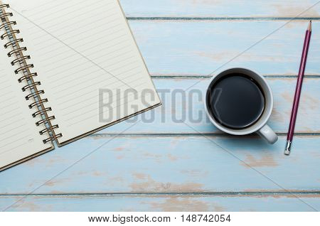 Top view Coffee with diary and red pencil on sky blue wooden floor.