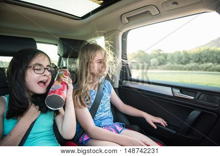Two girls having fun on a backseat of a car