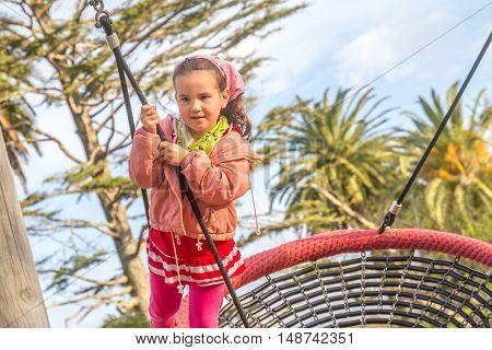 Challenging playground installation with nests and ropes for children to clamber. outdoor child girl portrait enjoying her time on the playground
