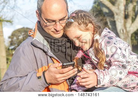 young happy man having fun with his little cute blond daughter taking selfie photo with mobile phone enjoying together outdoor in park