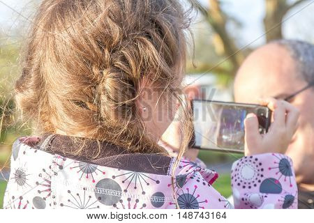 young blond girl taking photos of her dad on mobile phone, enjoying family time outdoors in park