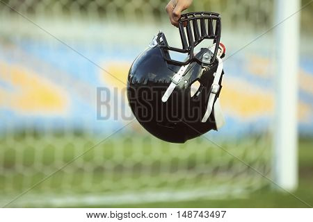 Male hand holding rugby helmet