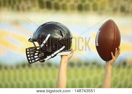 Male hands holding rugby helmet and ball