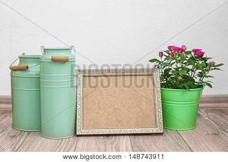 Roses in bucket, watering cans and photo frame on floor