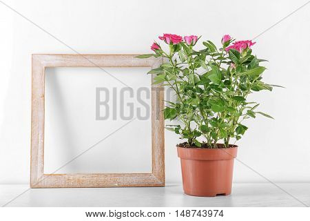Vase with roses and photo frame on table