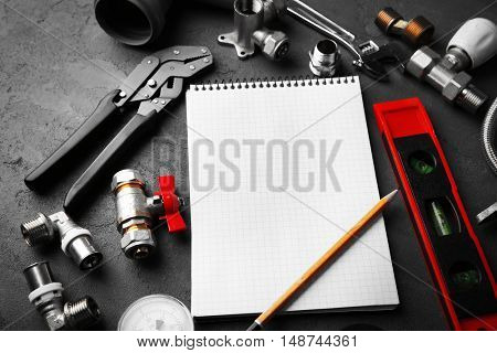 Notebook and plumber tools on concrete structure background