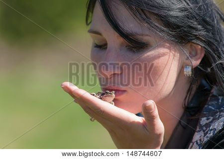 girl holds a frog in his palm
