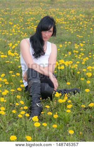 girl sitting on spring meadow with dandelions