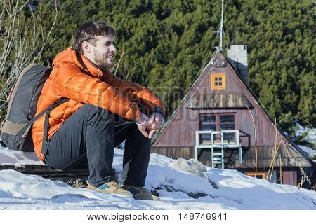 Backpacker is resting at mountain hut background in winter