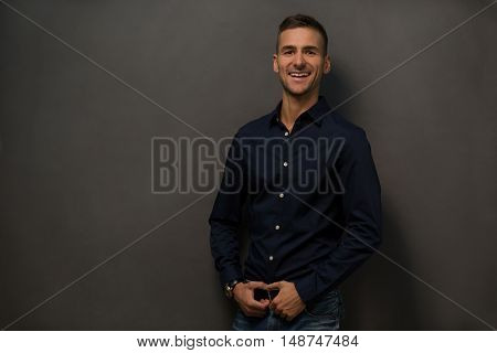 Close up picture of happy smiling mans face in studio. Handsome man with short haircut toothy smiling for camera while posing over grey background. Fashion or vogue concept.