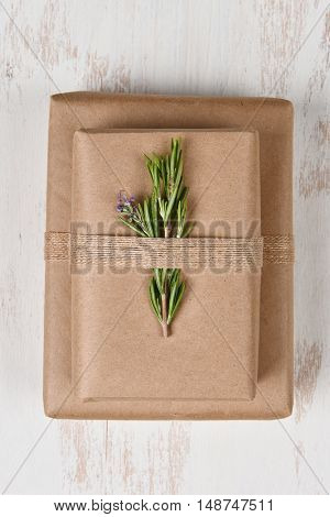 Plain brown paper wrapped Christmas presents on a rustic white background.