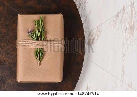 Plain brown paper wrapped Christmas presents on a dark round surface and rustic white background.