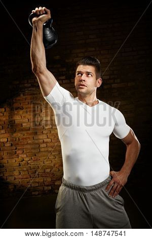Muscular young man doing kettlebell workout indoors.