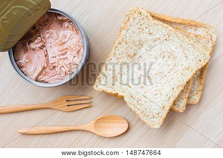 bread and tuna on wood table background / top view