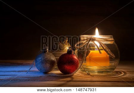 christmas baubles and candle on wood table wiht moon light at night