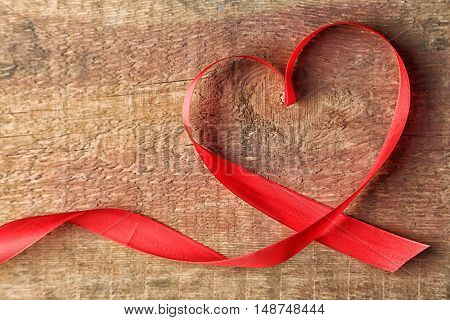 Heart shaped red ribbon on wooden background