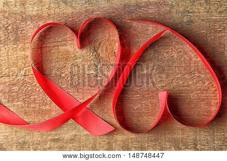 Heart shaped red ribbons on wooden background