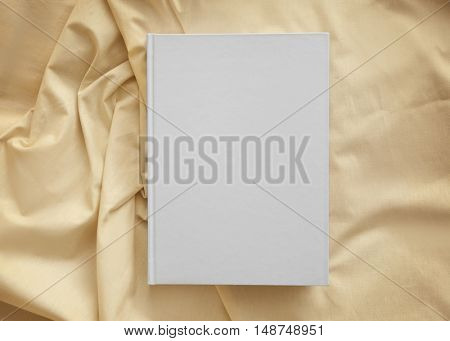 White closed book on light crumpled sheet