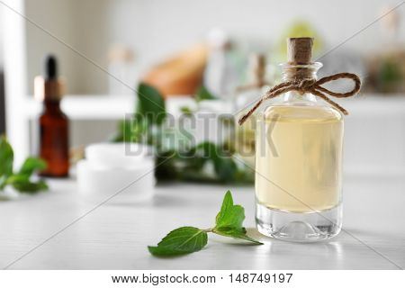Bottle with mint oil and fresh leaves on blurred room background