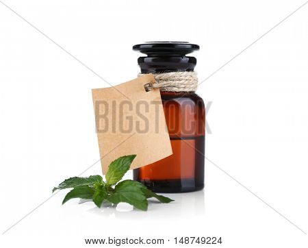 Bottle of mint oil and fresh leaves on white background