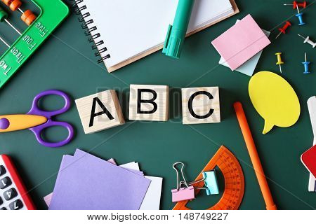 Composition of colourful stationery and word ABC on chalkboard
