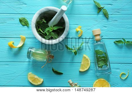 Bottles with mint oil and mortar with fresh leaves on wooden background, top view