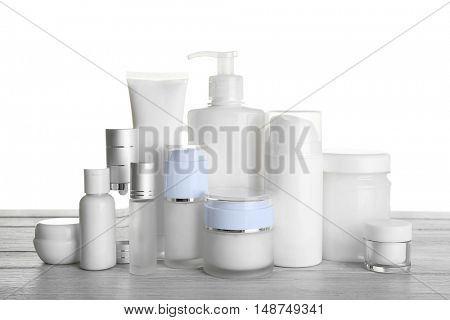 Different cosmetic bottles on table on white background