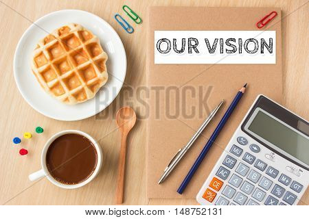 our vision text message on paper book and office supplies, pen, coffee on wood desk , copy space / business concept / view from above, top view