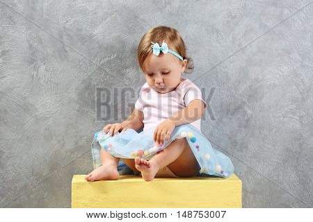 Little fashion-girl sitting on yellow box on gray wall background