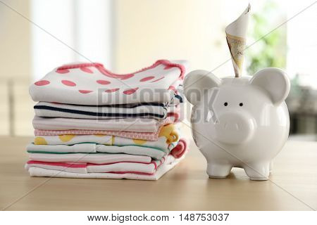 Stacks of baby linen and money box on the table