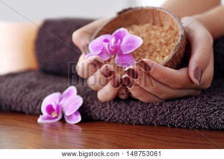 Female hands with brown manicure holding sea salt in bowl, closeup