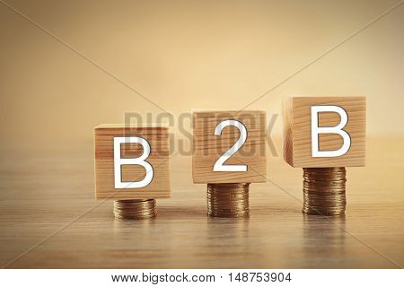 Wooden cubes with space for text and coins on beige background. Money concept
