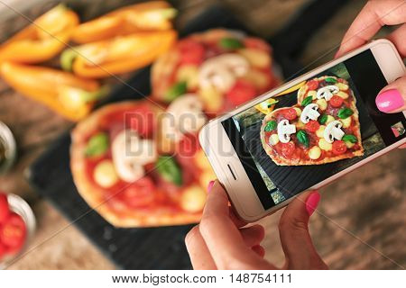 Female hands taking picture of tasty pizza