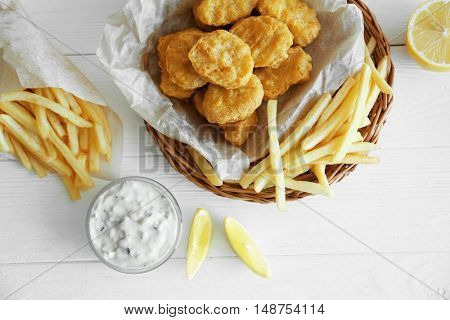Tasty chicken nuggets with lemon, fries and sauce on table