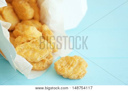 Tasty chicken nuggets in paper box on table