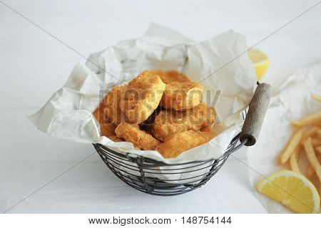 Tasty chicken nuggets in basket and lemon on table