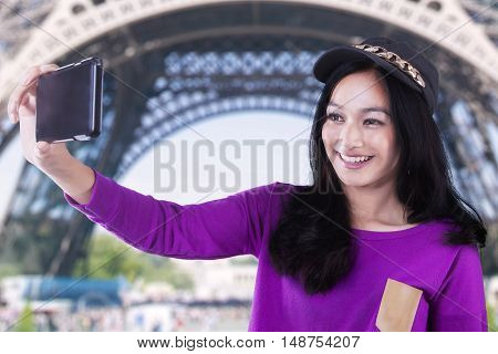 Picture of a beautiful teenage girl using smartphone to take selfie photo at Eiffel Tower